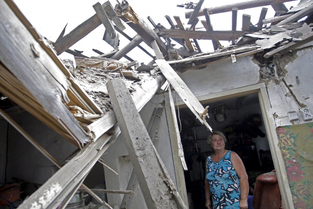 Woman inspects debris while standing inside her house, which, according to locals, was damaged by recent shelling, on the outskirts of Donetsk, Ukraine
