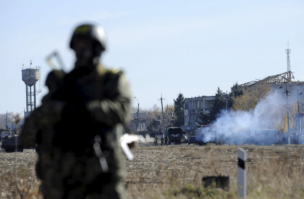 Servicemen stand guard near the territory of a military depot, where recent explosions took place, in Svatove in Luhansk region